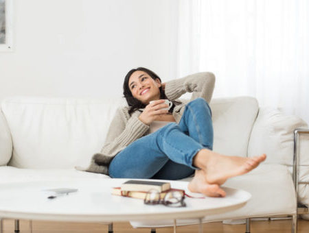 woman sitting on couch drinking coffee